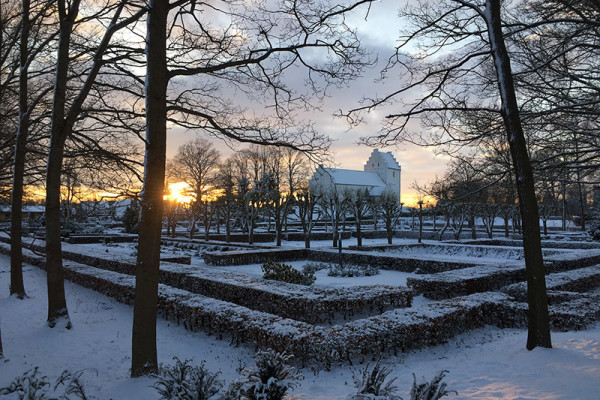 Hvalsø Kirke og kirkegård med sne og sol i baggrund