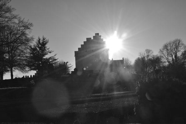 Sort hvidt billede af Hvalsø Kirke med solen som modlys