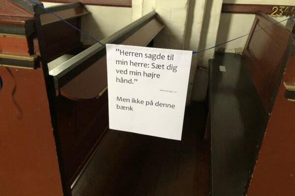 """Billede af stolerækken. Der er opsat tekst på afspærring """"Herren sagde til min herre: Sæt dig ved min højre hånd - Men ikke på denne bænk""""."""